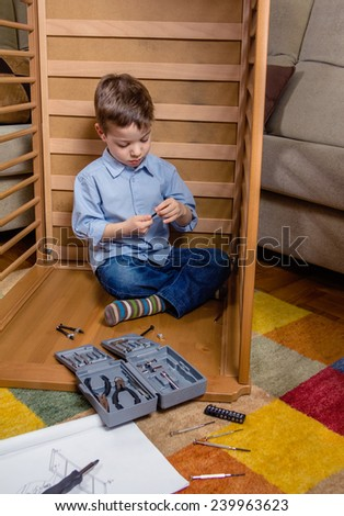Portrait of cute kid assembling with tools a new furniture for home. Family leisure concept