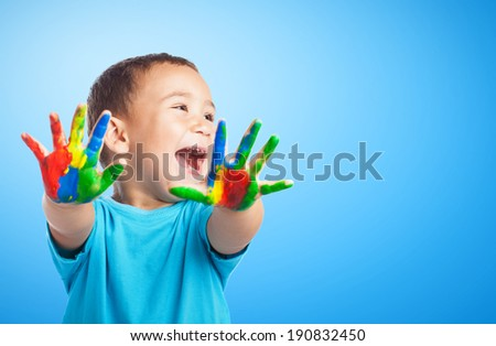 portrait of cute kid having fun with hands paint - stock photo