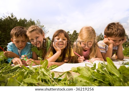 Portrait of cute kids reading books and drawing in natural environment together - stock photo