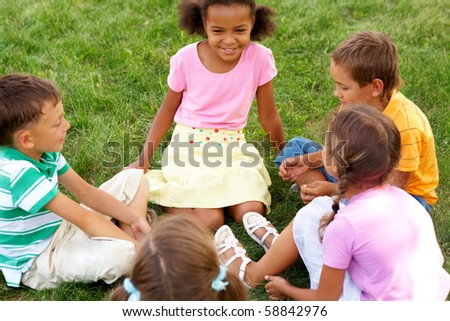 Portrait of cute kids seated on green grass and chatting - stock photo