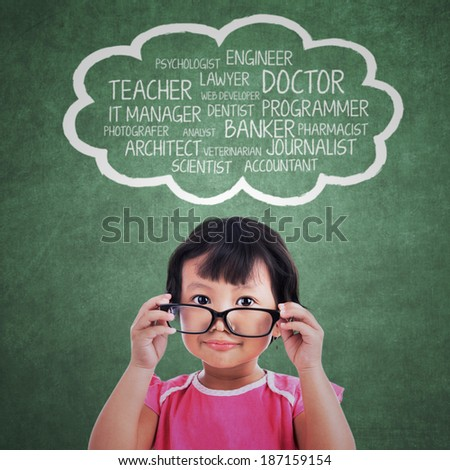 Portrait of cute kindergarten with her ideals over her head - stock photo