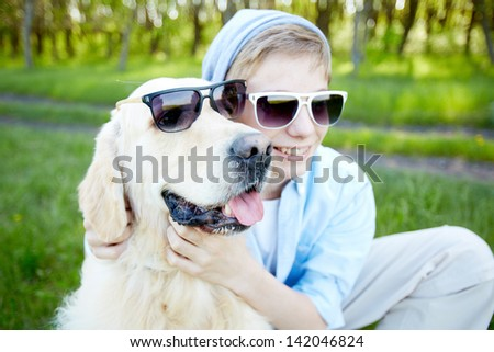 Portrait of cute lad and his fluffy friend in sunglasses outdoors - stock photo