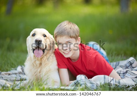 Portrait of cute lad and his friendly pet lying on plaid