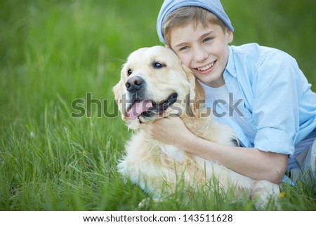 Portrait of cute lad embracing his fluffy friend while lying on grass - stock photo