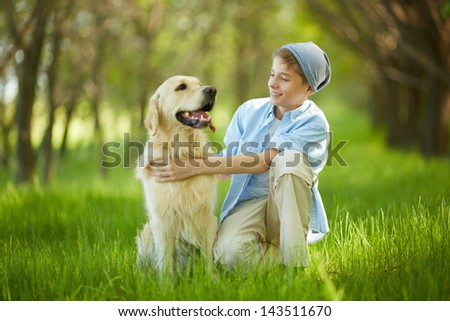 Portrait of cute lad embracing his white Labrador and looking at it