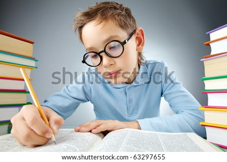 Portrait of cute lad in eyeglasses reading book - stock photo
