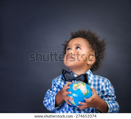 Portrait of cute little African boy holding in hands small globe on blackboard background, looking up, back to school concept - stock photo