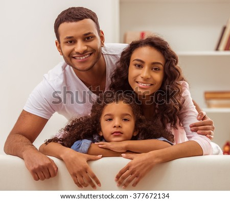Portrait of cute little Afro-American girl and her beautiful young parents posing, looking at camera and smiling. - stock photo