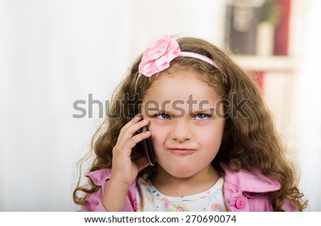 portrait of cute little angry girl using cell phone - stock photo