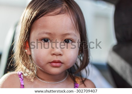 portrait of cute little asian girl with baby powder on her face