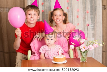 Portrait of cute little baby girl celebrating first birthday with her brother and sister. Happy children having birthday party with birthday cake, balloons decorations and flowers.