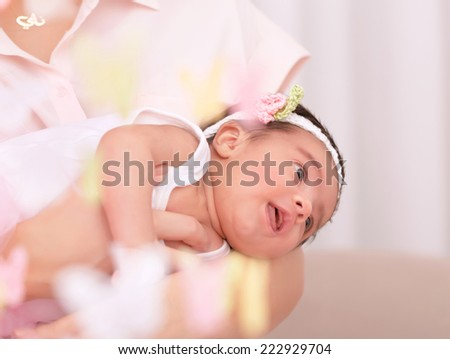 Portrait of cute little baby girl on mothers hands, young happy family spending time at home, tenderness and love concept  - stock photo