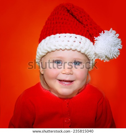 Portrait of cute little baby girl wearing Santa hat isolated on red background, funny festive costume for Christmas celebration - stock photo