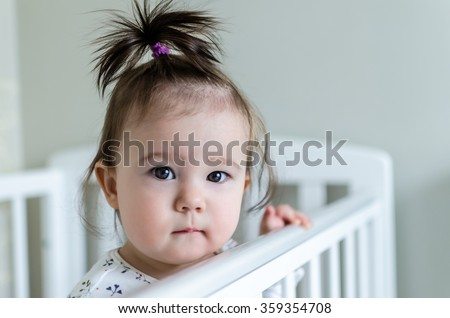 Portrait of cute little baby girl with black brunette hair in white patterned long sleeved bodysuit staying in her bed at home and looking at camera with smart and curious beautiful hazel brown eyes - stock photo