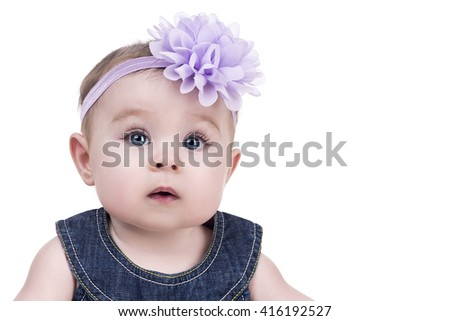 portrait of cute little baby girl with bow flower on her head. kid looks into the camera with admiration. child girl with big blue eyes. happy family concept
