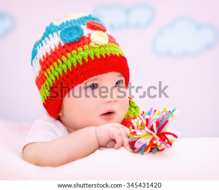 Portrait of cute little baby wearing colorful warm hat relaxing in cozy children's room, healthy lifestyle, happy carefree childhood - stock photo