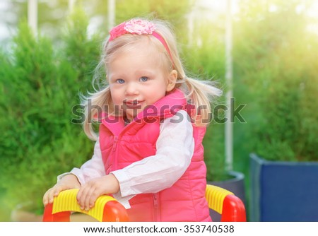 Portrait of cute little blond girl having fun on playground in warm sunny day, adorable kid playing outdoors, happy carefree childhood - stock photo