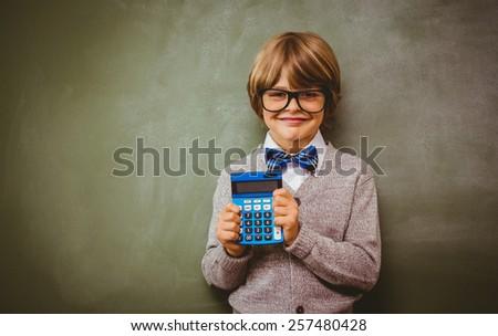 Portrait of cute little boy holding calculator in front of blackboard - stock photo