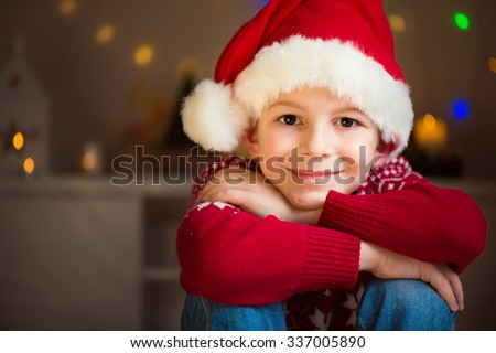 Portrait of cute little boy in red hat waiting Santa Claus