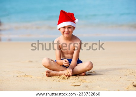 Portrait of cute little boy in Santa hat on tropical vacation