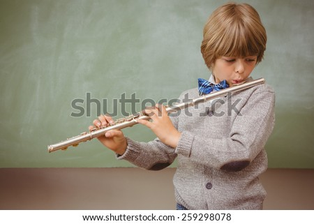 Portrait of cute little boy playing flute in classroom - stock photo