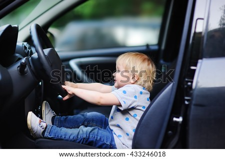 Portrait of cute little boy playing in fathers car - stock photo