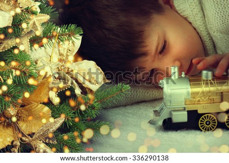 Portrait of cute little boy playing with Christmas light at home. - stock photo