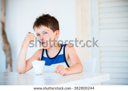 Portrait of cute little boy refuses to eat delicious yogurt - stock photo