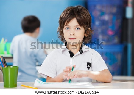 Portrait of cute little boy with paper and sketch pen at desk in preschool - stock photo