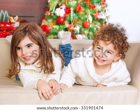 Portrait of cute little brother and sister having fun at home, spending happy winter holidays, with pleasure playing games on the sofa near Christmas tree - stock photo