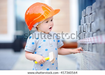 Portrait of cute little builder in hardhats with hammer working outdoors