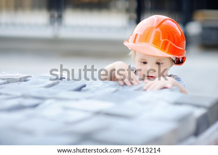 Portrait of cute little builder in hardhats working outdoors