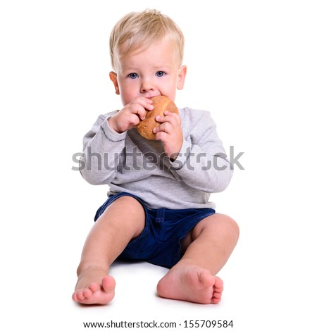 portrait of cute little caucasian baby sits and eats bread. isolated on white background. baby 1 year - stock photo