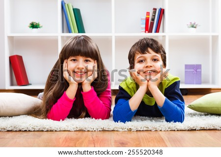 Portrait of cute little girl and boy lying down on carpet in the living room.Carefree childhood - stock photo