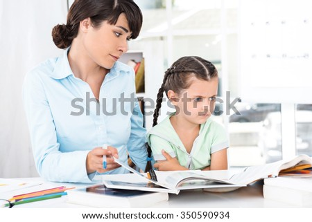 Portrait of cute little girl and her mother while working day. Business woman helping daughter to do homework. Girl is bored - stock photo