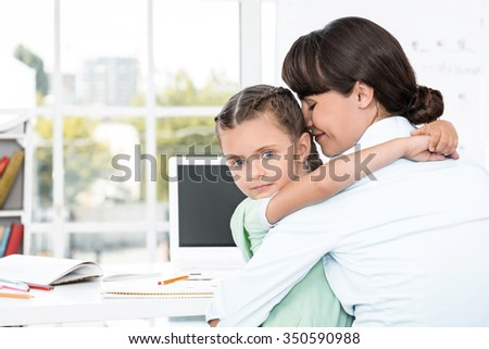 Portrait of cute little girl and her mother while working day. Business woman trying to amuse daughter and hugging her - stock photo