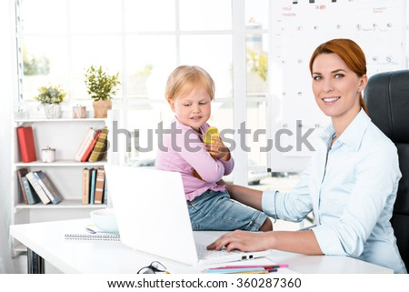 Portrait of cute little girl and her mother while working day. Business woman trying to amuse her daughter. Girl looking at laptop - stock photo