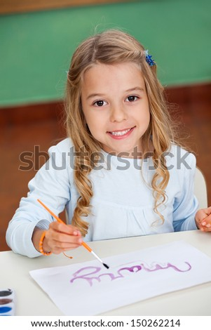 Portrait of cute little girl drawing at desk in kindergarten