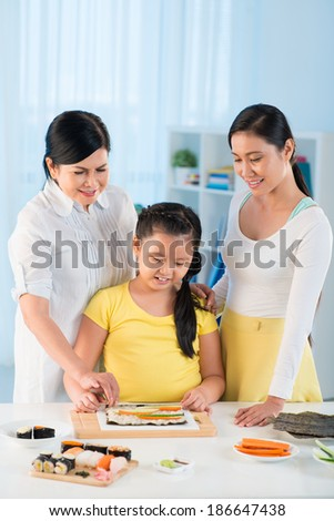 Portrait of cute little girl, her mother and grandmother cooking sushi together - stock photo
