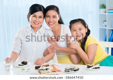 Portrait of cute little girl, her mother and grandmother sitting at the served table and looking at camera