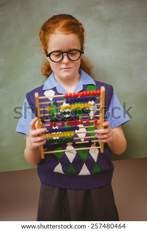 Portrait of cute little girl holding abacus in front of blackboard - stock photo