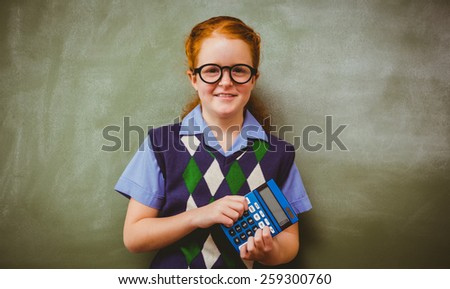 Portrait of cute little girl holding calculator in front of blackboard - stock photo