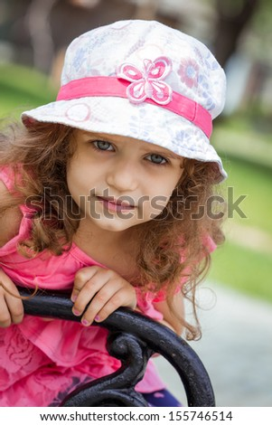 Portrait of cute little girl in a park. Close-up of beautiful child, outdoors