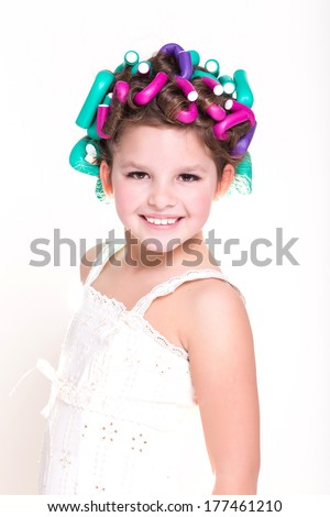 Portrait of Cute little girl in curlers and pajamas, skincare kid beauty and glamour. Funny baby girl with hair curlers. Lovely little girl smiling. Pajamas party. Isolated, studio, white background. - stock photo