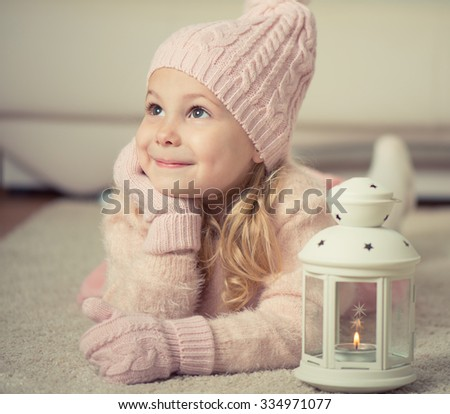 Portrait of cute little girl in hat and gloves at Christmas time