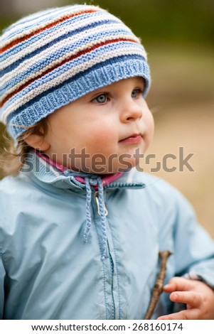 Portrait of cute little girl in nature. Side view, she is looking ahead at something or someone. Selective focus, shallow depth of field - stock photo
