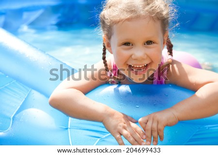 Portrait of cute little girl in swimming pool outdoors