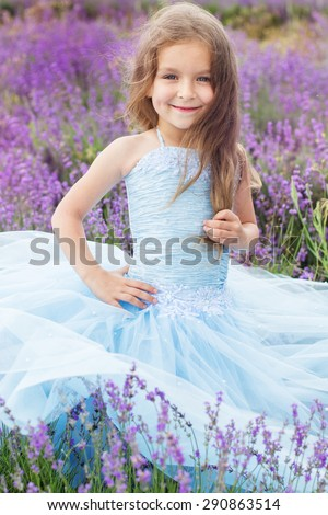 Portrait of cute little girl is resting in a lavender field  - stock photo