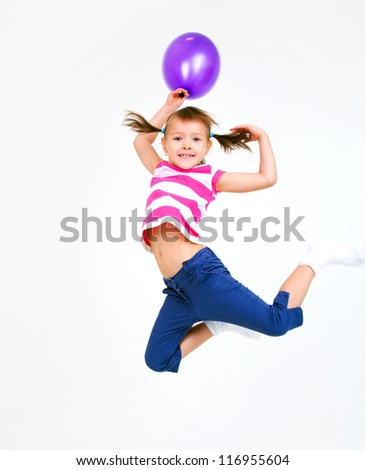 Portrait of cute little girl jumping  with violet  balloons - stock photo