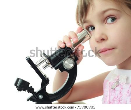 Portrait of cute little girl leaned against eye to microscope - stock photo